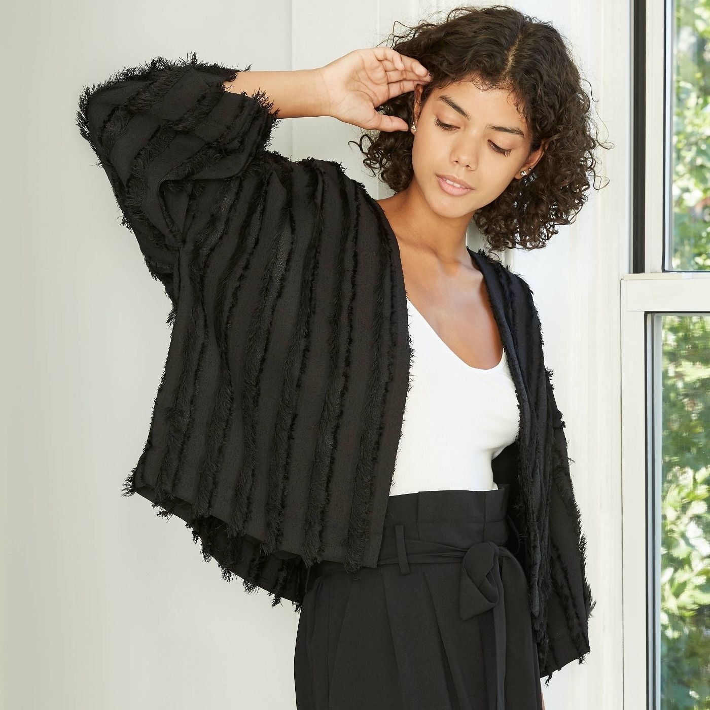 Model in textured fringe overcoat