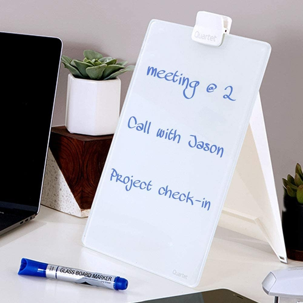 The dry-erase easel on a desk with a marker in front of it
