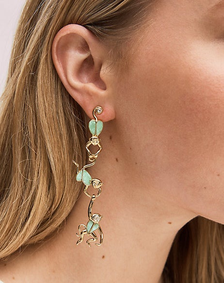 A model wearing the dangle earrings designed to look like three monkeys hanging from one another. They have heart-shaped resin bellies