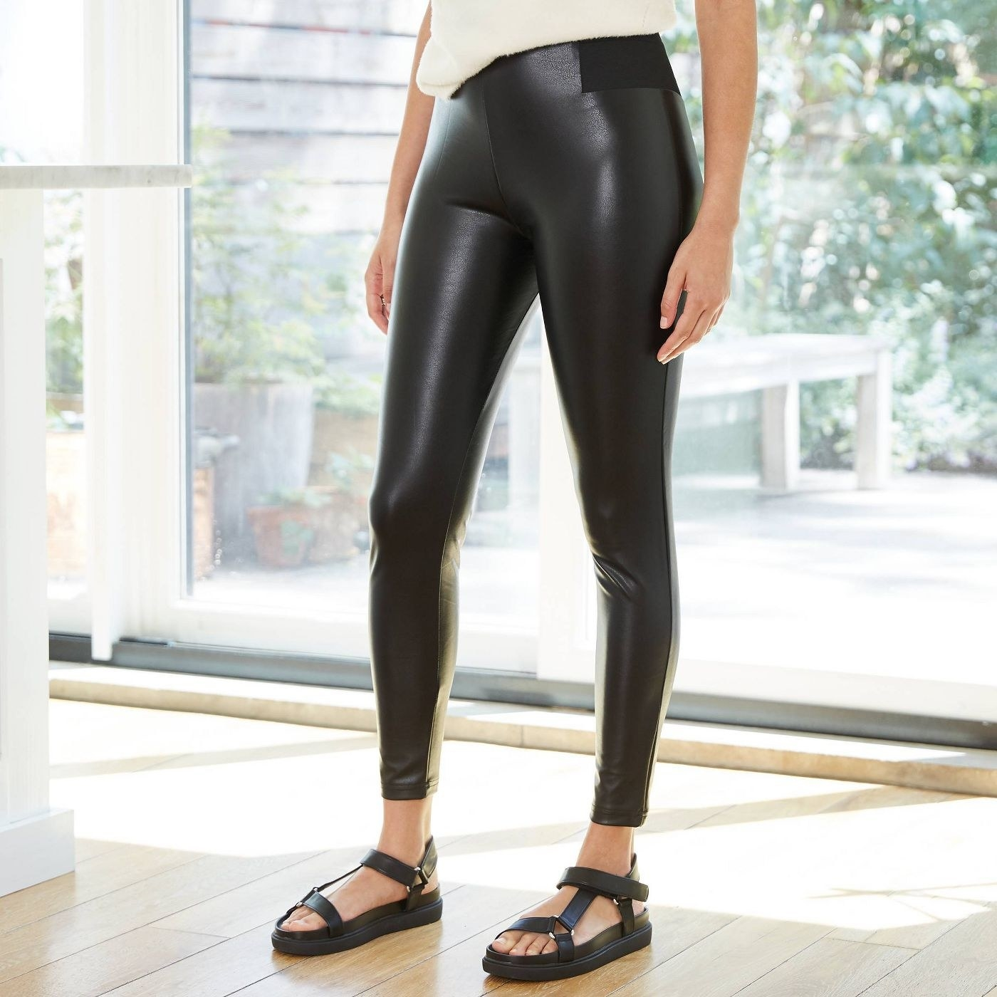 Model in black faux leather leggings
