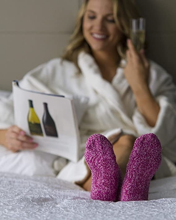 A person wears the fuzzy socks in bed while sipping on champagne