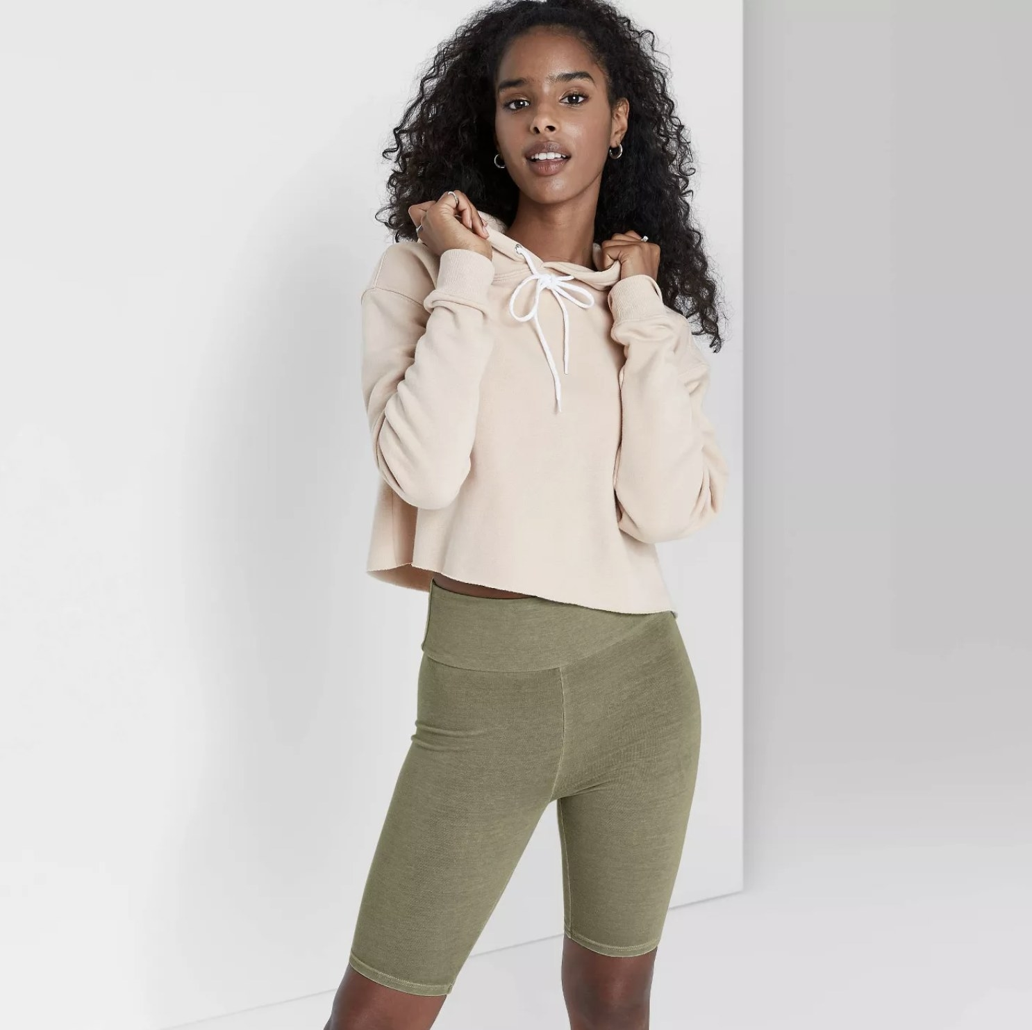 Model is wearing olive green biker shorts with a cream cropped hoodie