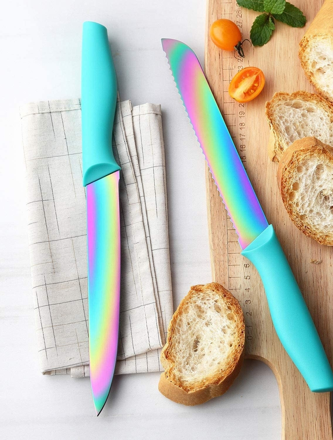 Two rainbow knives with turquoise handles and sliced bread on a cutting board.