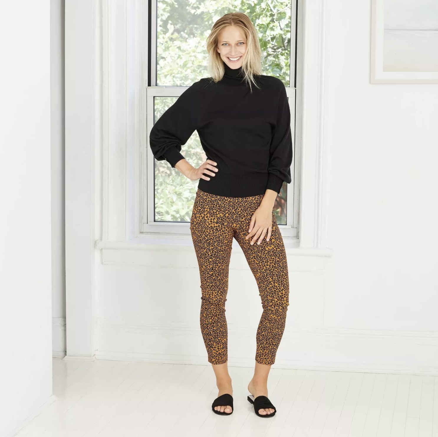 Model is wearing gold leopard print cropped pants, a black turtleneck sweater, and black slides