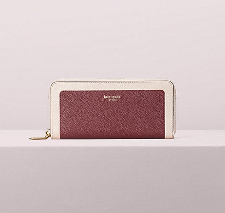 The burgundy wallet with a cream border and a zipper