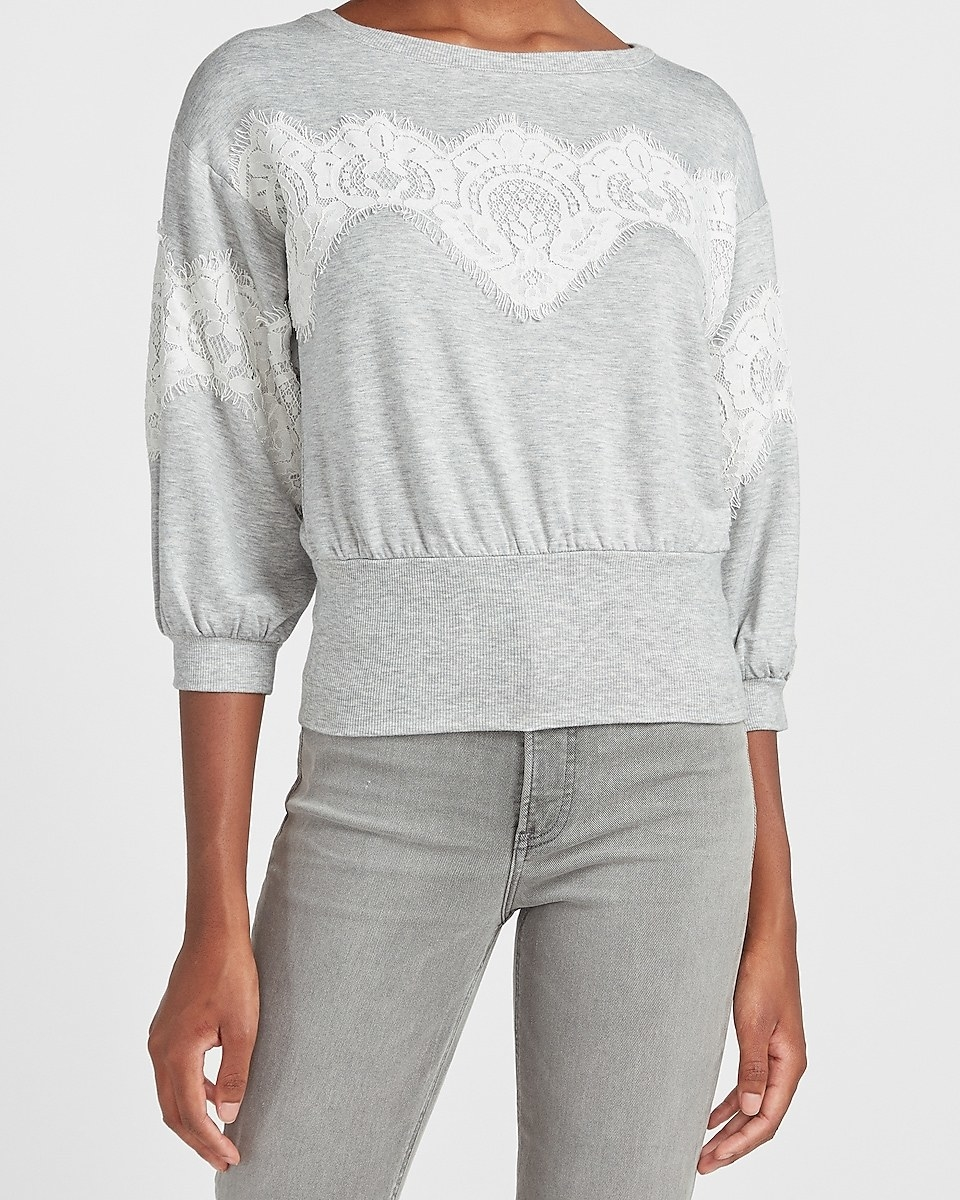 A model wearing the light gray three-quarter sleeve sweatshirt with white lace and a thick banded waist