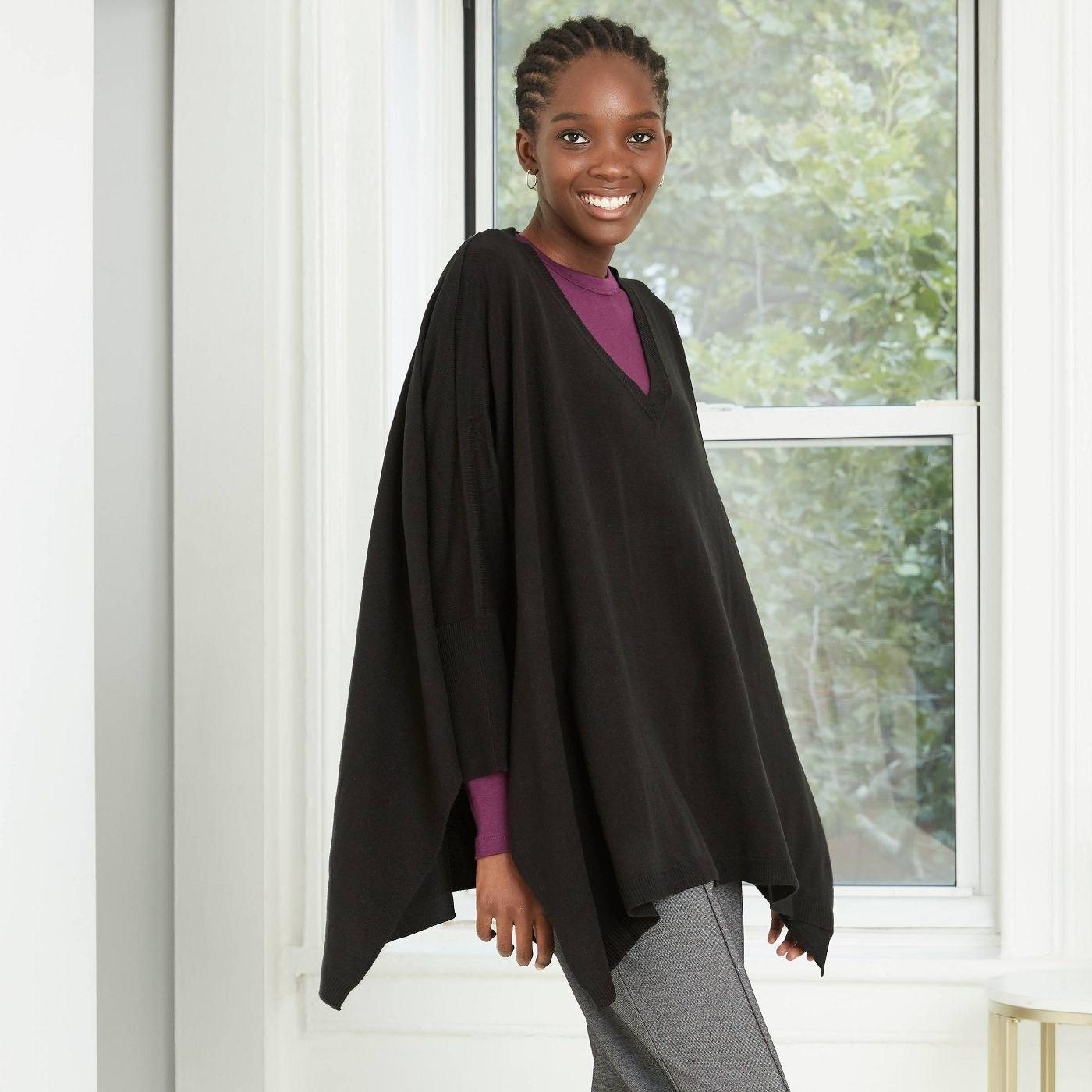 Model in a black V-neck poncho with a purple top underneath