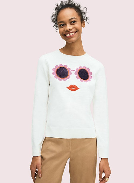 A model wearing a white crewneck long sleeve with a floral sunglass and lipstick design
