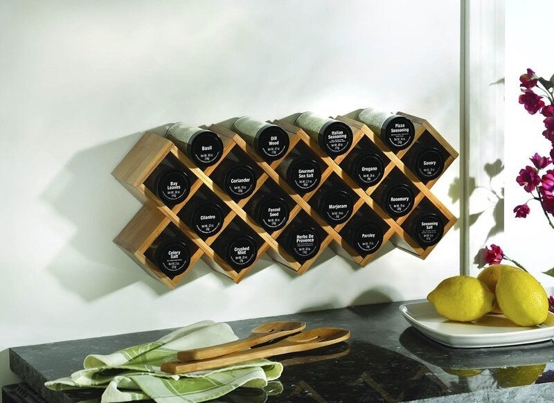 A wooden wall-mounted spice rack holding 18 labeled jars of spices