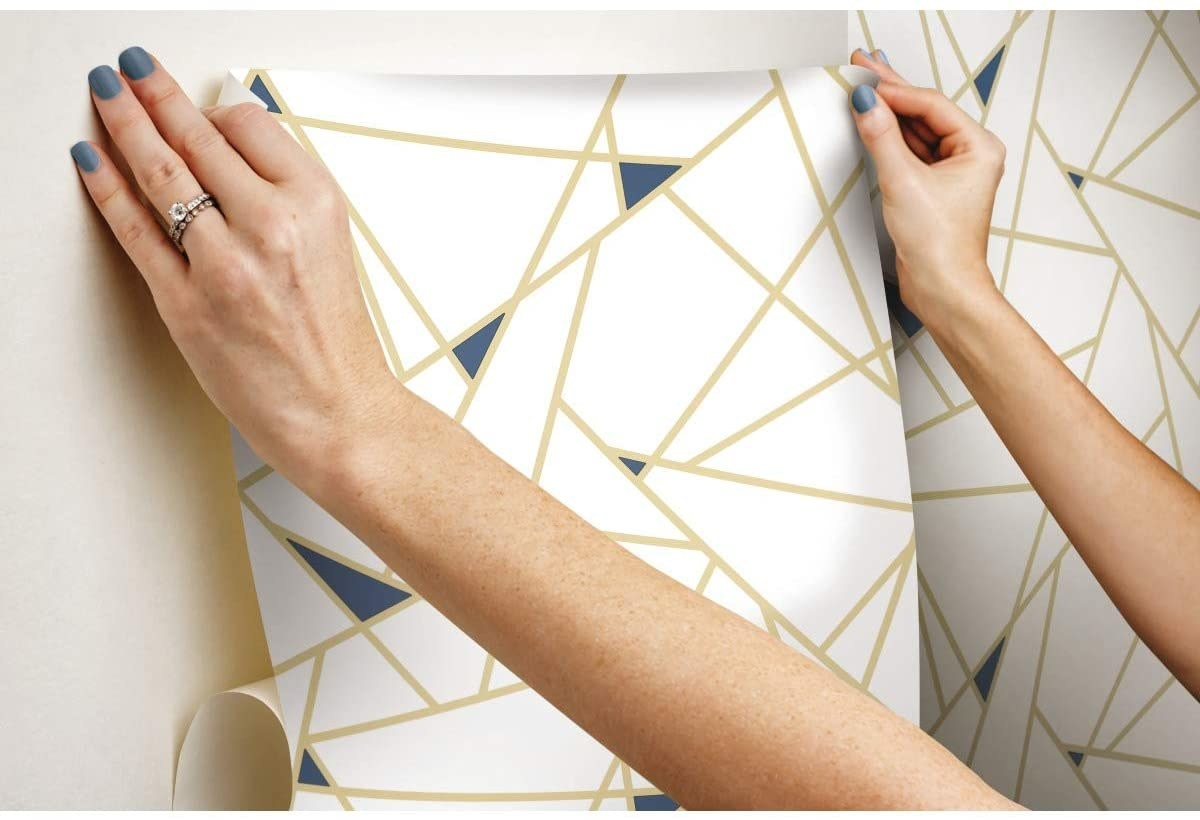 A person applying the wallpaper to their wall