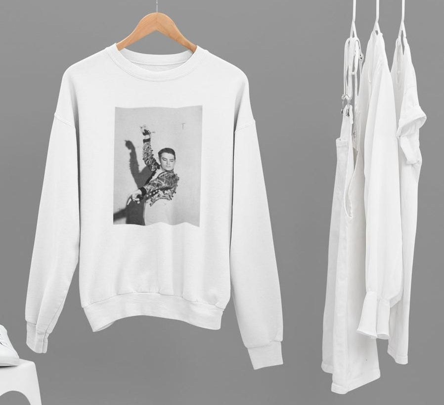 A white long sleeve sweatshirt with a black and white photo of a young Walter Mercado