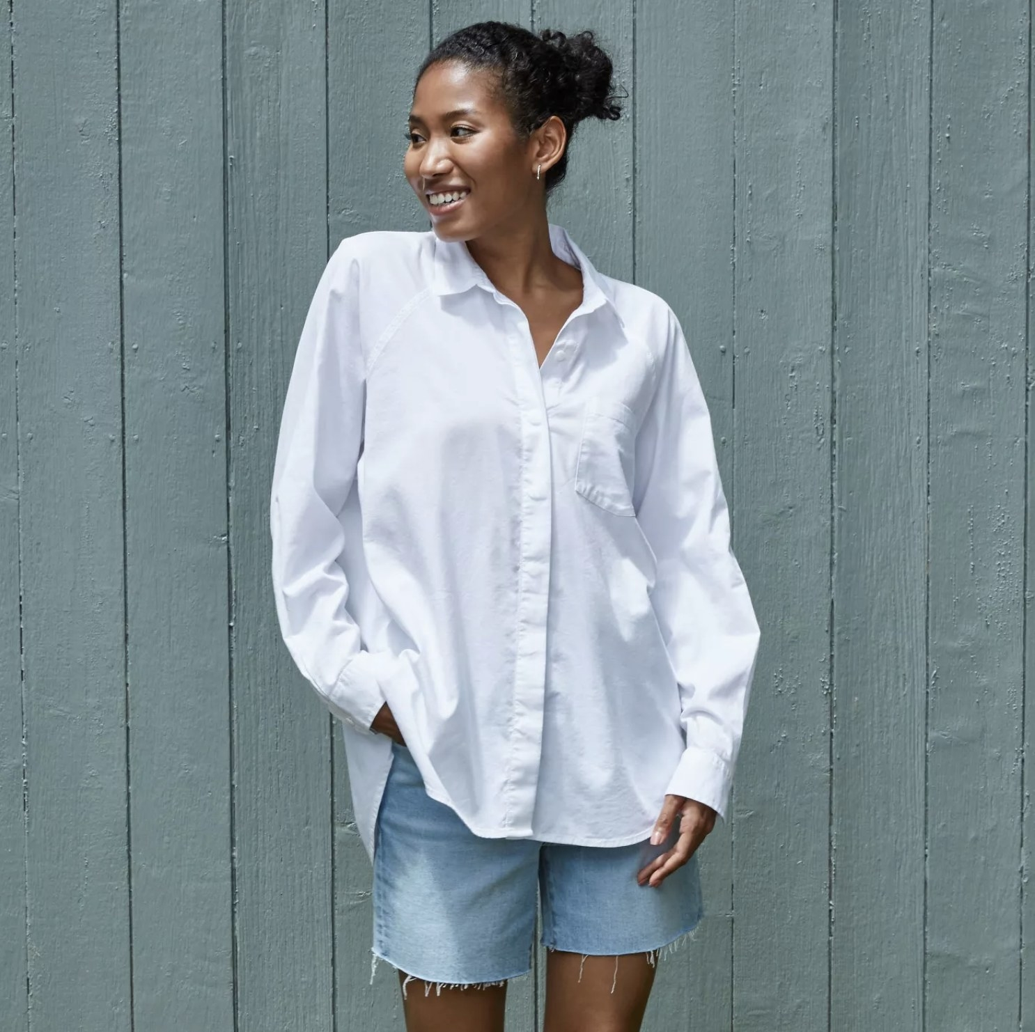 Model is wearing a white oversized button-down long-sleeve boyfriend shirt and jean shorts