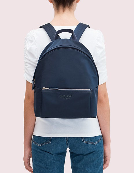A model wearing the navy blue backpack, which has a main pocket and a front pocket