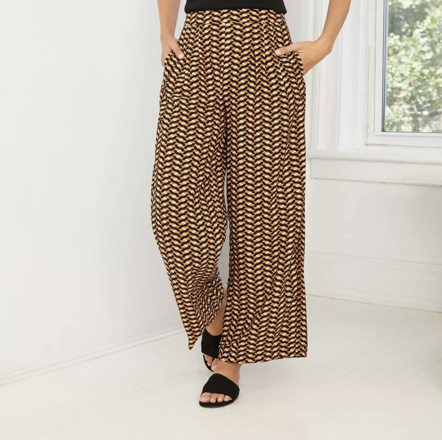 Model is wearing a pair of black and gold geometric print wide-leg pants with pockets and black slides