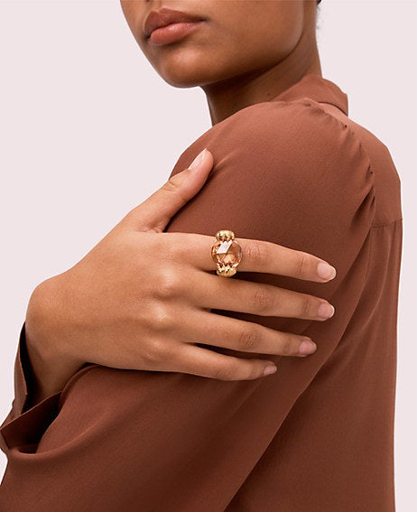 The gold-plated brass ring designed to look like animal paws clutching a jewel