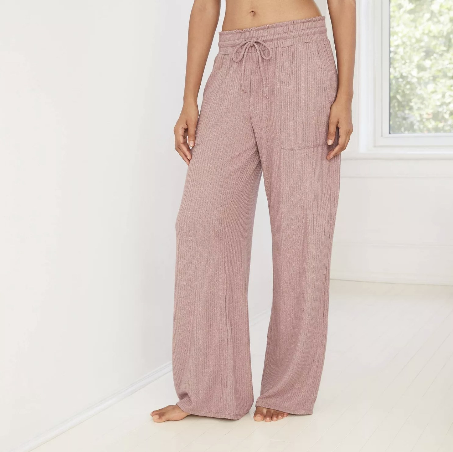 Model is wearing a light mauve wide leg pant with drawstring and pockets