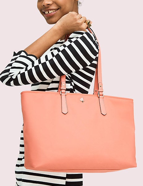 A model carrying the large peach colored tote bag on their shoulder