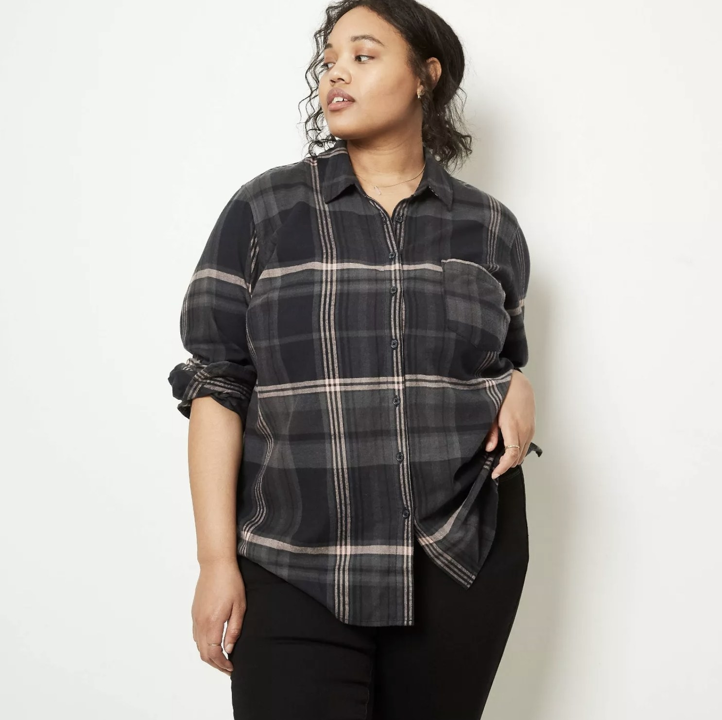 Model is wearing a black plaid button-down long sleeve shirt and black pants