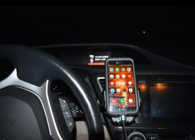 Reviewer's smartphone propped on a blacks smartphone holder next to a steering wheel