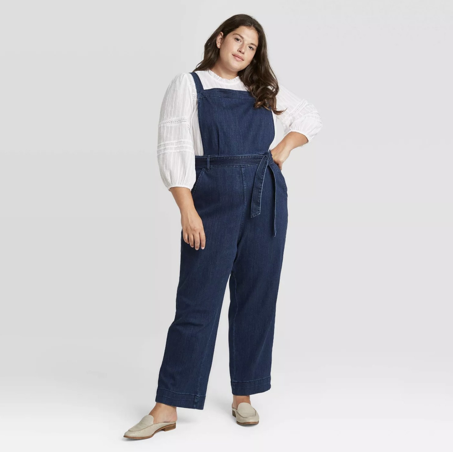 Model is wearing a dark wash denim overall with a tie front detail and white peasant top underneath with cream loafers