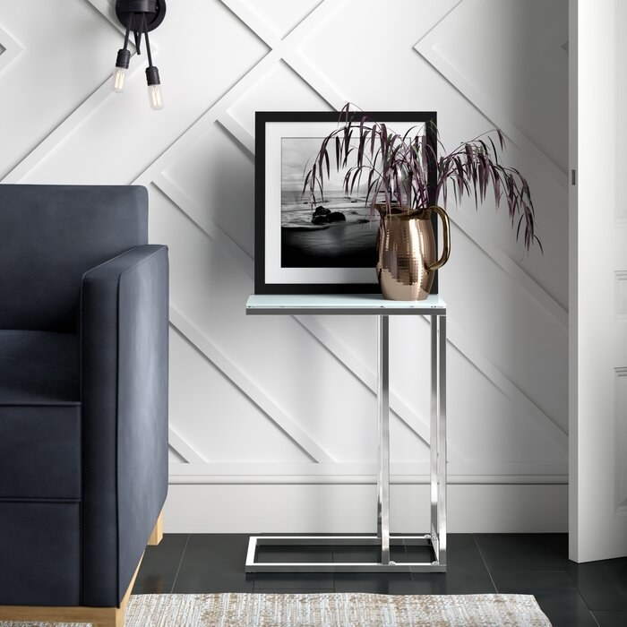 The silver C-shaped end table with metal legs