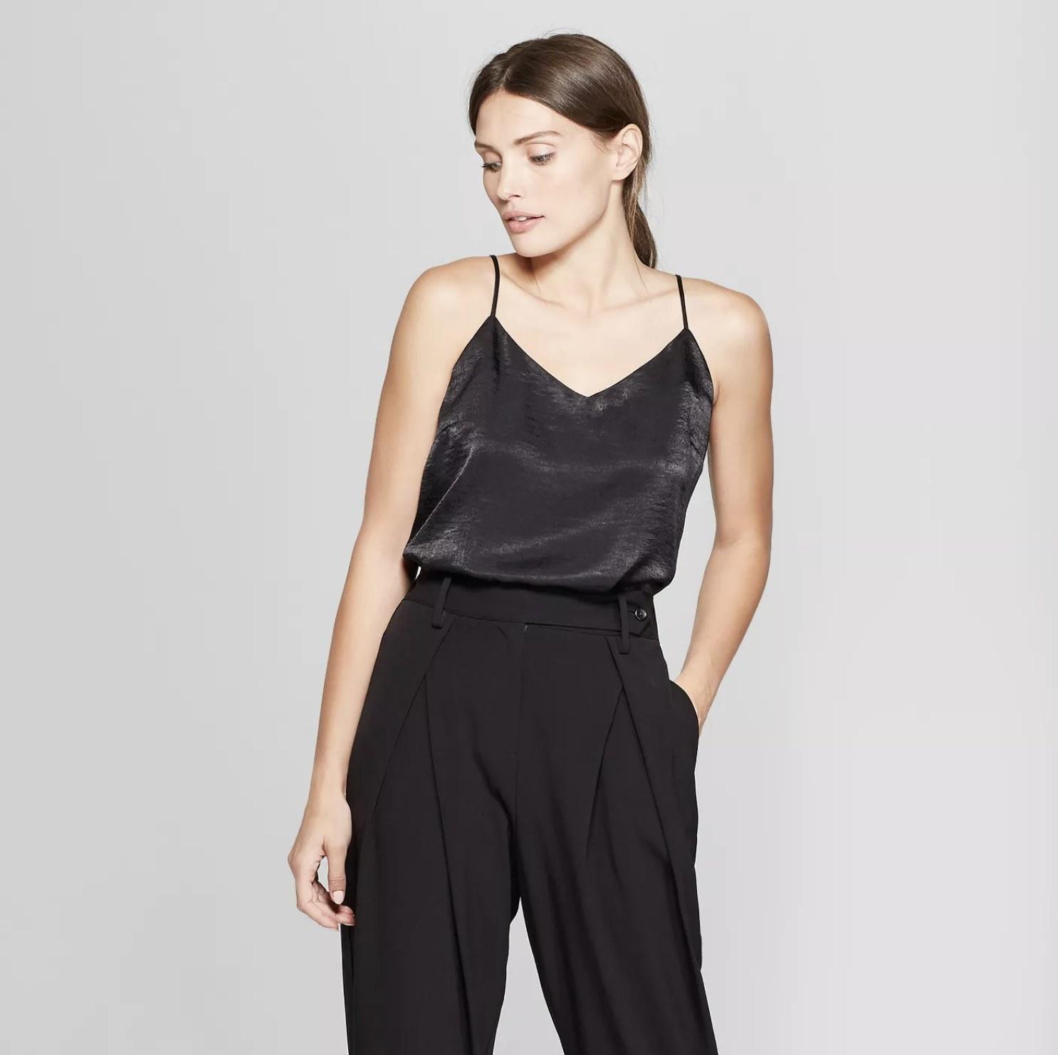Model is wearing a black woven blouse tank with black slacks