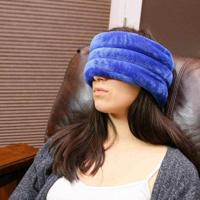 A model wearing the thick blue plush wrap around the top of their head and eyes