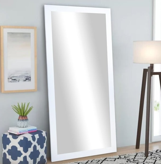 The white-framed full-length mirror