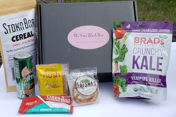 The Keto Black box with keto snacks like crunchy kale, a vanilla Stoka bar, a Fat Snax peanut butter cookies, and pink grapefruit Perrier