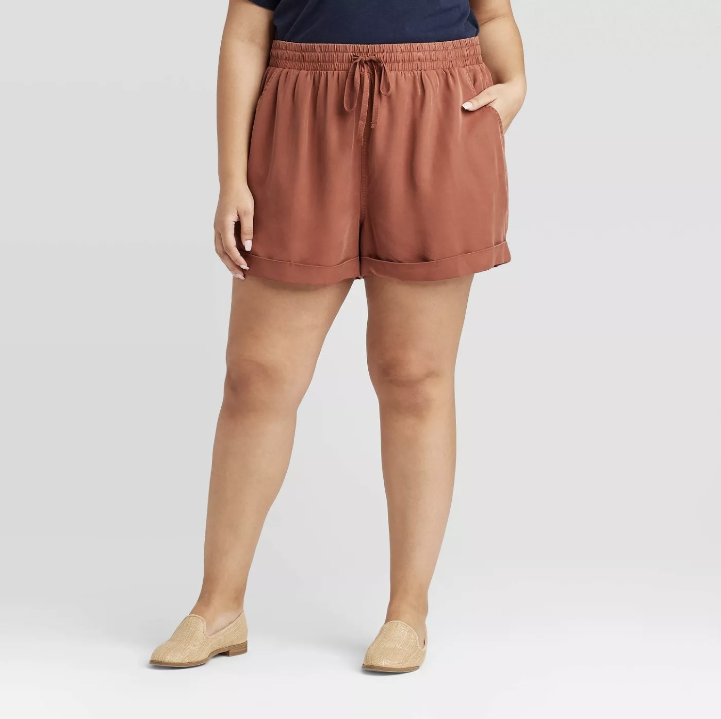 Model is wearing rust mid rise shorts with an elastic tie waist and cream loafers