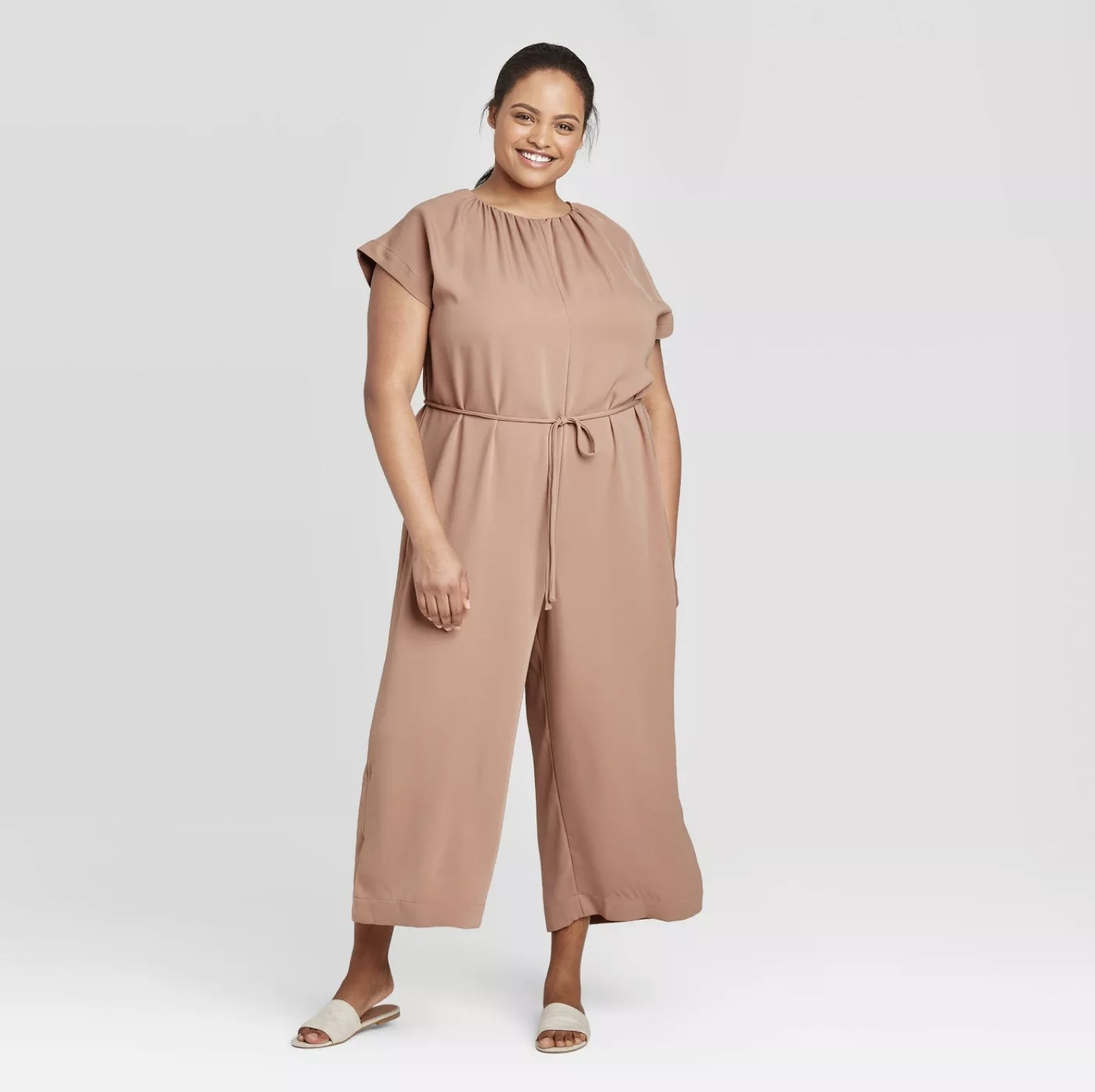 Model is wearing a mauve short sleeve ankle length jumpsuit with gathered waist details and grey slides