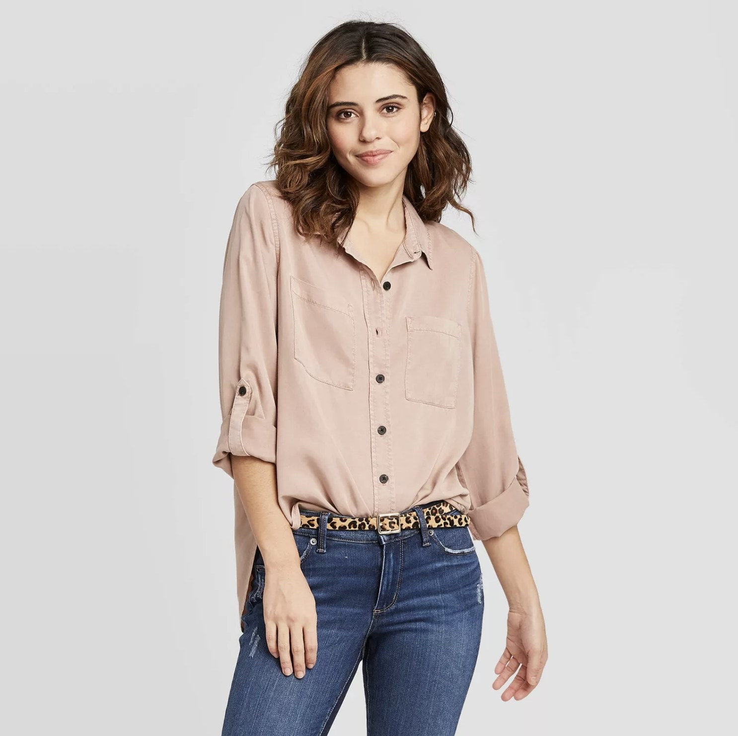 Model is wearing a mauve long-sleeve button-down shirt with dark blue jeans and a cheetah print belt
