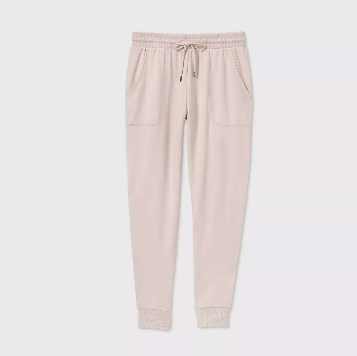 A pair of blush pink joggers with pockets and an elastic waist band