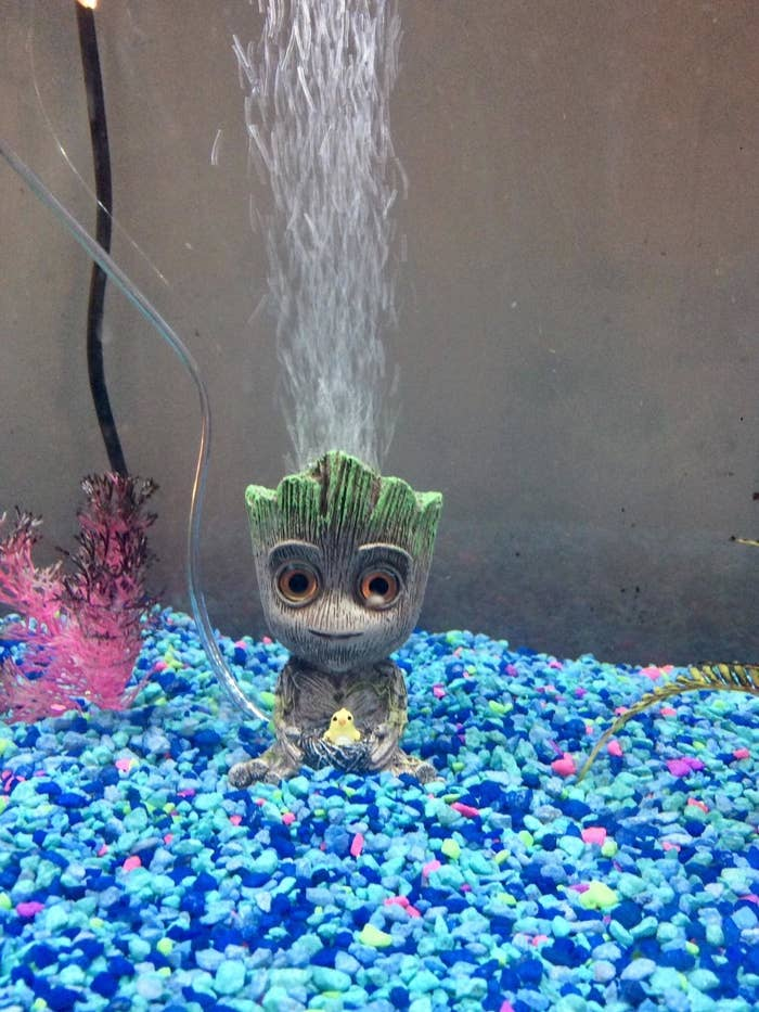 Reviewer's Baby Groot air bubbler sits in gravel at the bottom of a fish tank
