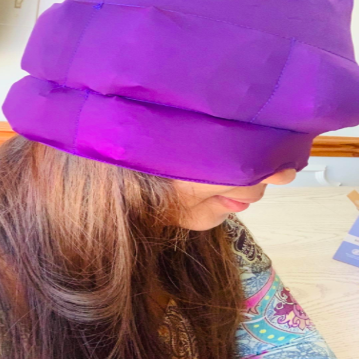 A different reviewer wearing the cap, which has an indent for going around your nose, over their head and eyes