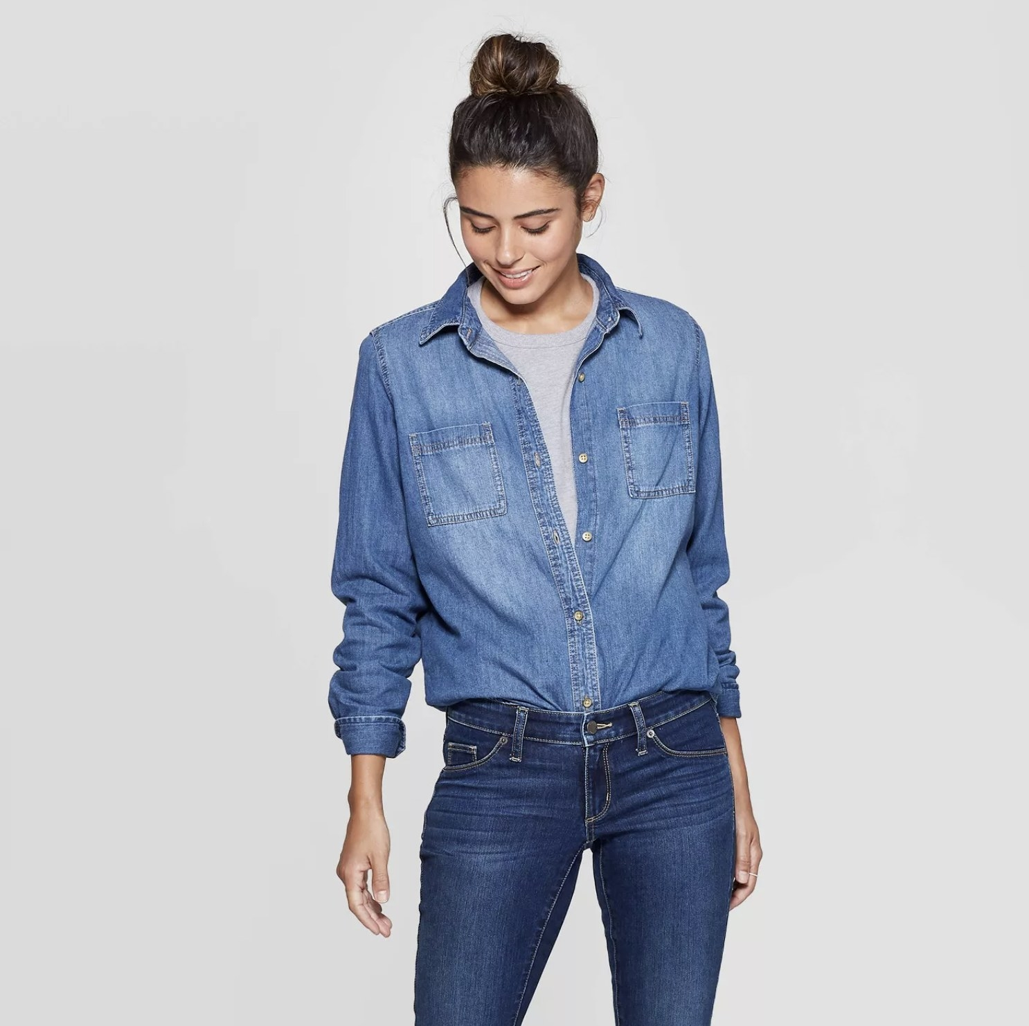 Model is wearing a long sleeve button down denim shirt with a grey shirt underneath and dark blue jeans