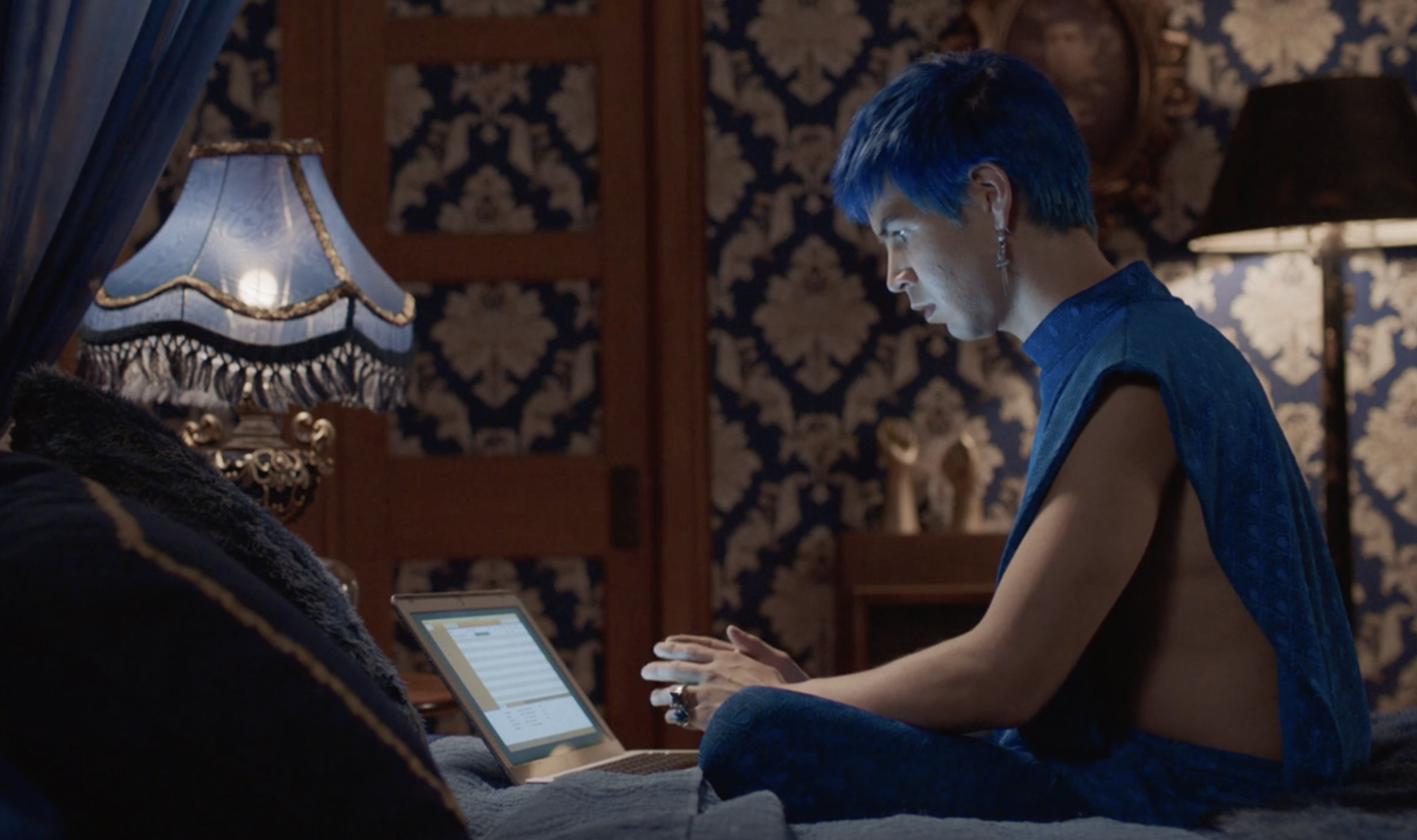 Andres on his computer while wearing a blue sleeveless shirt that's completely open on the sides