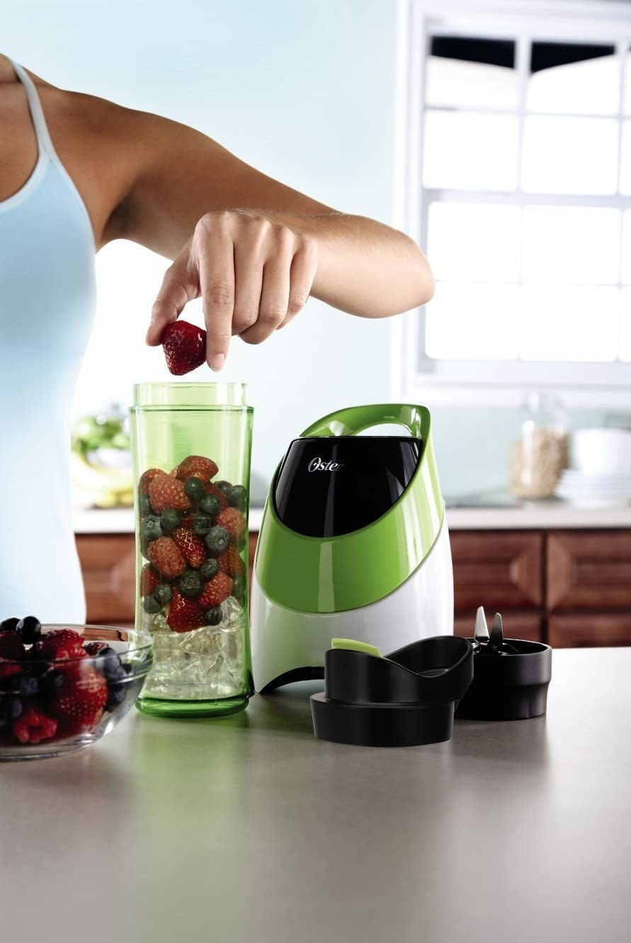 A model filling the bottle with ice and berries as it sits next to the Oster blender with the lid and blades