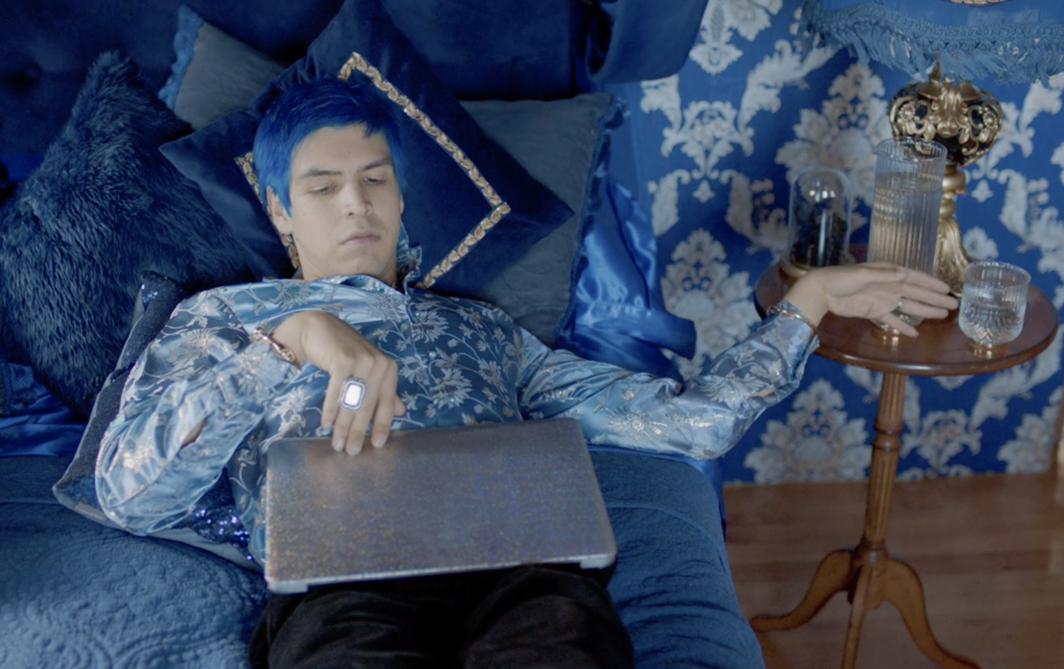 Andres laying in bed with his laptop while wearing a blue floral silk button-up
