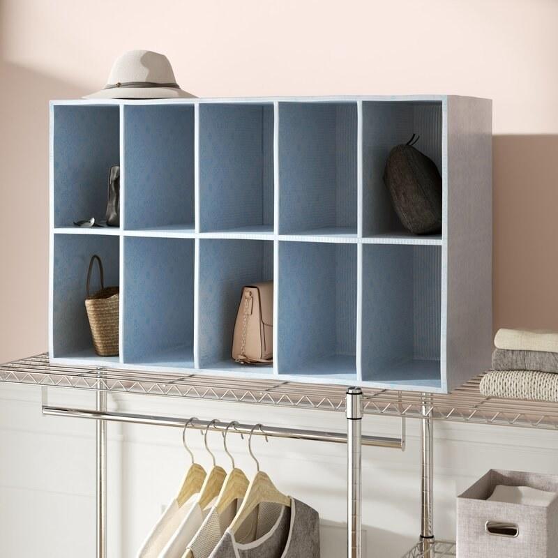 A light blue unit with 10 cubbies on a closet shelf holding purses and a hat