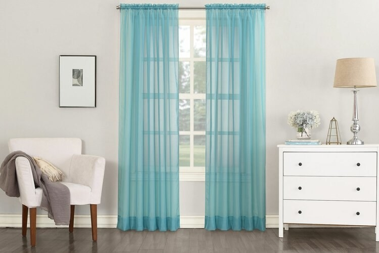 Slightly see-through blue curtains draped from the top of a window to the floor, extending beyond the side edges of the window, and making it the focal point of a neutral-toned room, between a sitting chair and dresser