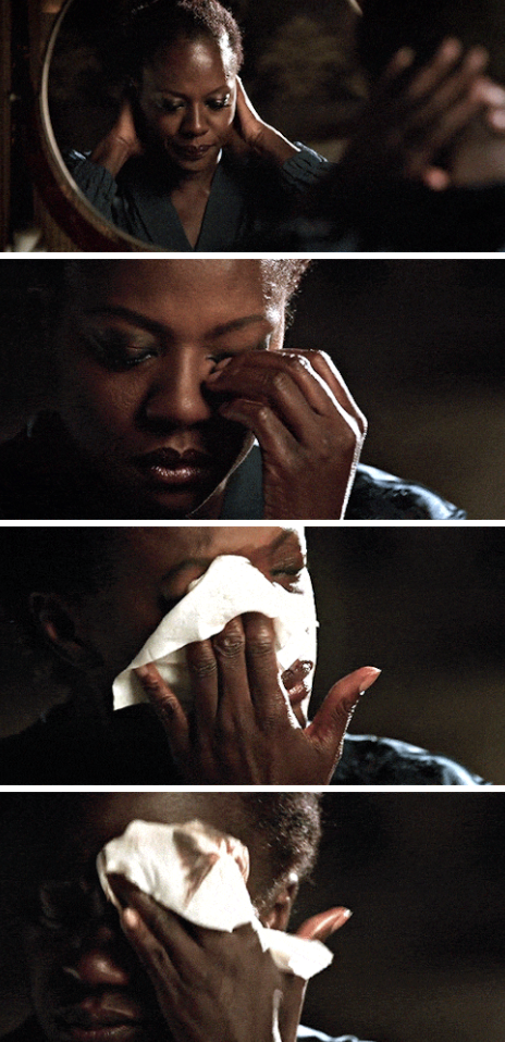 Annalise taking off her wig and makeup in front of the mirror