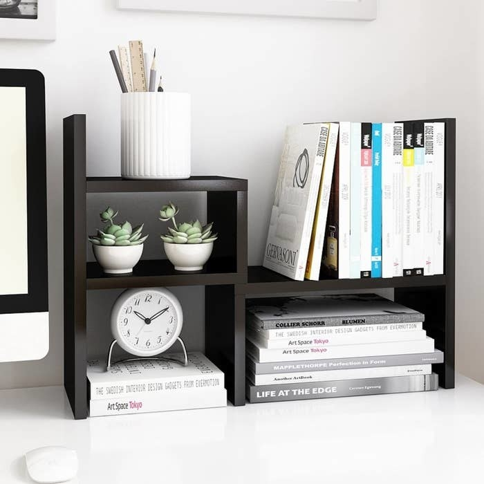 The wood shelf in black with three different areas to store things with books. plants, a clock, and other trinkets in it