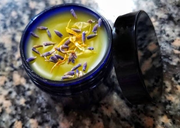 A tub of the balm topped with herbs or petals
