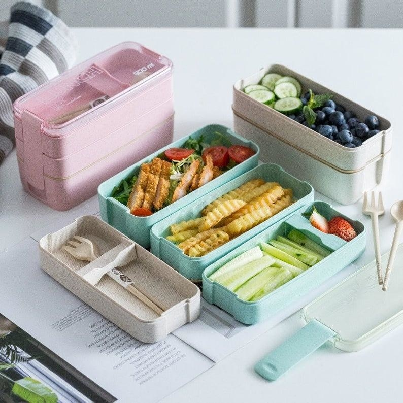 The lunch boxes with three stackable compartments displayed variously, two of the lunch boxes are filled with food and one is stacked up and empty