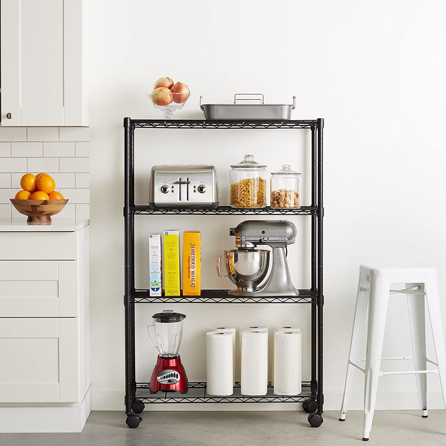A four-tiered metal storage rack beside a counter with kitchen supplies on each shelf