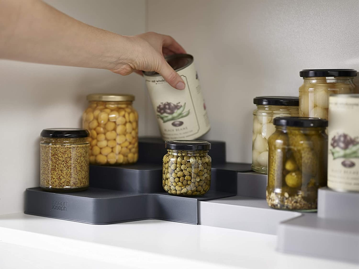 A person placing a can of beans on a small shelf in a cupboard