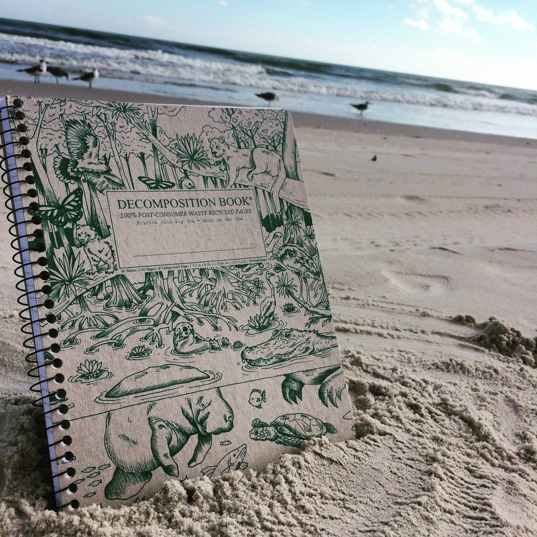 The notebook displayed upright in the sand at the ocean with manatees, sea turtles, mangroves and other wildlife on the cover