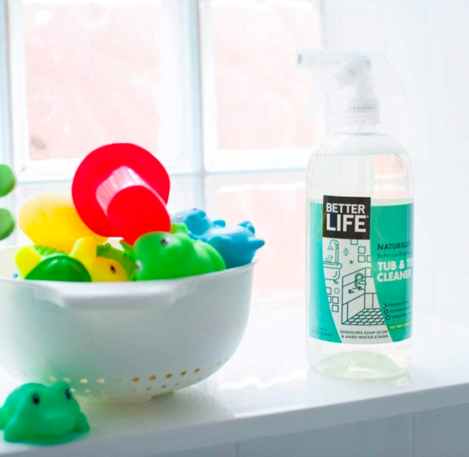 Clear bottle of Better Life Tub & Tile Cleaner next to a windowsill and strainer with bathtub toys