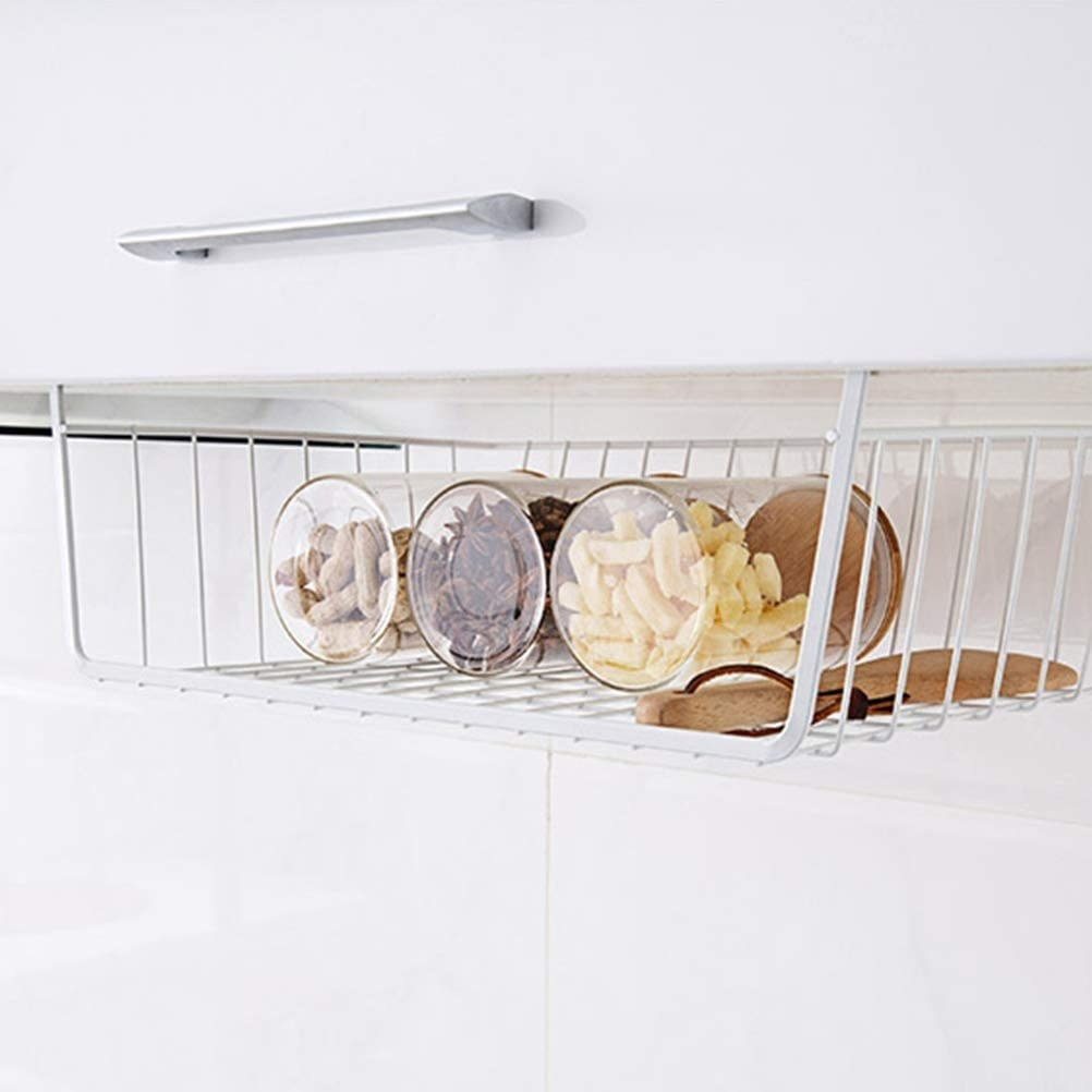 A wire storage basket hanging from a kitchen cupboard with jars of food placed inside
